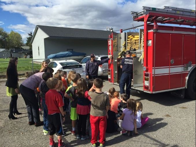 Firefighter with fire truck and group of children