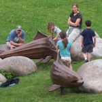 Family playing around rocks and dolphin sculptures Opens in new window
